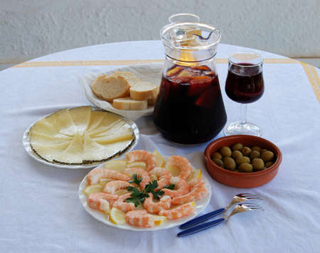 A selection of tapas with sangria and beer, King prawns with lemon, Sliced Manchego cheese, and green olive cocktail, Costa del Sol, Malaga Province, Andalucia, Spain, Western Europe  photo