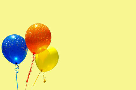 Three party baloons against a yellow background