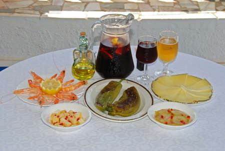A selection of tapas with sangria and beer, King prawns, pointed fried peppers and Manchego cheese, Manchego cheese with chilli, pickled cucumber with chilli, Costa del Sol, Malaga Province, Andalucia, Spain, Western Europe. photo