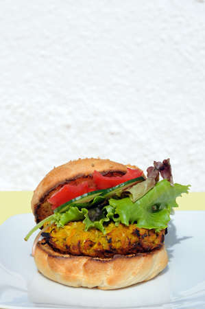 sesame seed bun: Vegetarian chickpea, sweetcorn and carrot burger with salad in a sesame seed bun, UK  Stock Photo