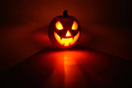 Eng gezicht gesneden in pompoen voor Halloween van binnenuit verlicht, West-Europa