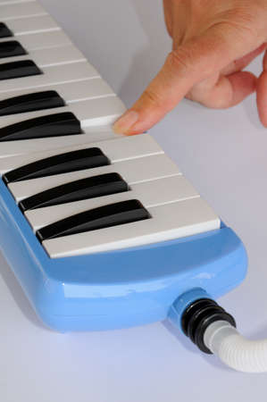 aerophone: Blue and white Pianica blow-organ with finger pressing middle C
