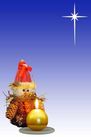Pinecone snowman ornament with a gold candle in the foreground and the star of Bethlehem to the rear  Stock Photo - 15217646