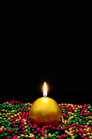 Round gold candle and shiny beads against a black background  Stock Photo - 15029734