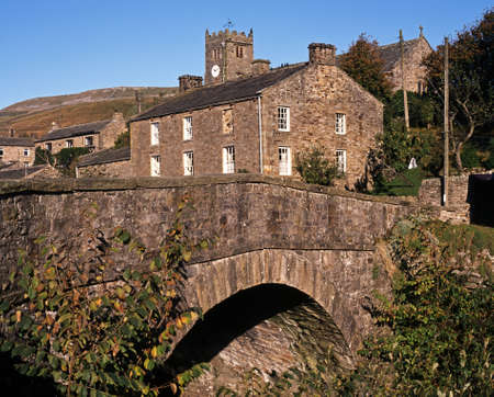 dales: Stone road bridge over Straw Beck with village and church to rear, Muker, Swaledale, Yorkshire Dales, North Yorkshire, England, UK, Great Britain, Western Europe  Stock Photo