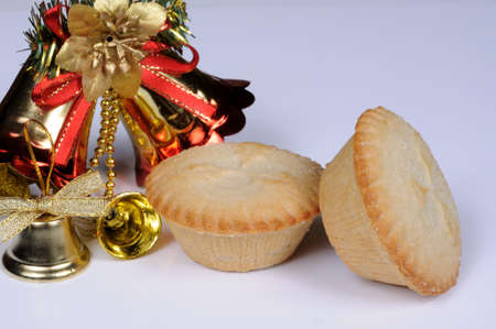 Two mince pies with Christmas bells to the rear against a grey background