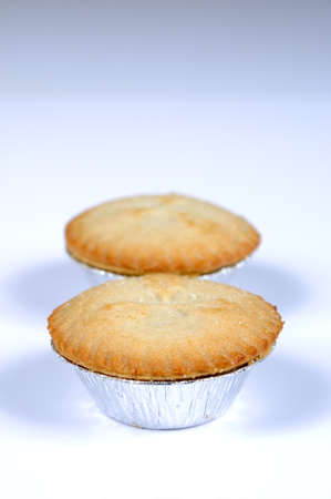 Two mince pies in foil cases against a grey background