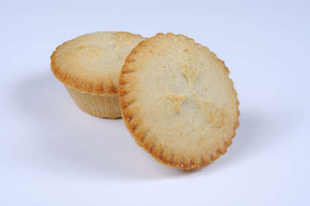 Two mince pies against a grey background