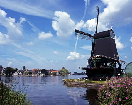 Windmill with Dutch village across river, Zaanse Schans, Holland, Europe  Stock Photo - 16590348
