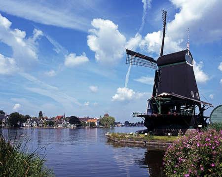 Windmill with Dutch village across river, Zaanse Schans, Holland, Europe Stock Photo - 16590348