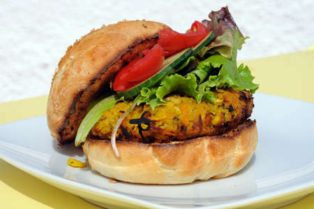 Vegetarian chickpea, sweetcorn and carrot burger with salad in a sesame seed bun, UK  Stock Photo