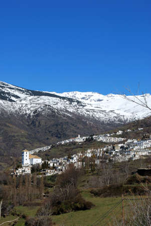General view of town with Capileira to and snow capped mountains to rear, Bubion, Las Alpujarras, Granada Province, Andalusia, Spain, Western Europe  photo