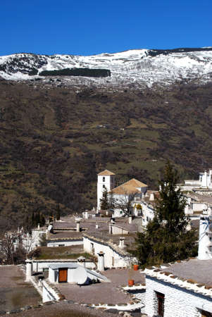 General view over town rooftops towards the snow capped mountains, Bubion, Las Alpujarras, Granada Province, Andalusia, Spain, Western Europe  photo