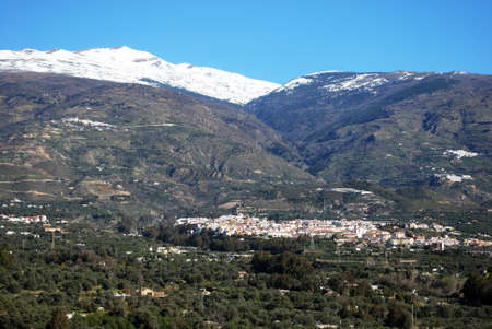 View of the town and countryside in the Vale of Lecrin with views towards the snow capped Sierra Nevada mountains, Orgiva, Vale of Lecrin, Las Alpujarras, Granada Province, Andalusia, Spain, Western Europe  photo