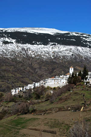 General view of village and snow capped mountains, Capileira, Las Alpujarras, Granada Province, Andalucia, Spain, Western Europe  photo