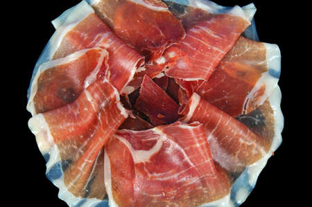 cured: Spanish cured ham on a black background  Stock Photo