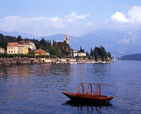 View of the lake and town with a traditional boat in the foreground, Lake, Como, Tremezzo, Lombardy, Italy, Europe. photo