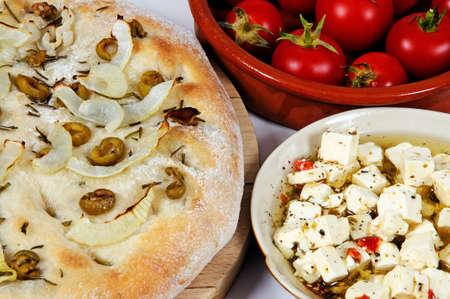 Olijf, ui en rozemarijn focaccia geserveerd met feta kaas en cherrytomaatjes
