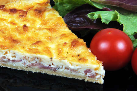 Quiche Lorraine with lettuce and cherry tomatoes on a black plate