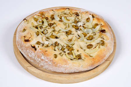 Italian Focaccia bread on a wooden chopping board topped with green olive, onion and rosemary against a white background