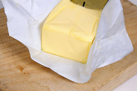 studio b: Block of English butter on a wooden chopping board