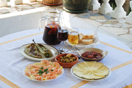 alfresco: A selection of tapas with sangria and beer, Fried green peppers, olive cocktail, Chorizo slices, Sliced Manchego cheese, Prawns, Costa del Sol, Malaga Province, Andalucia, Spain, Western Europe