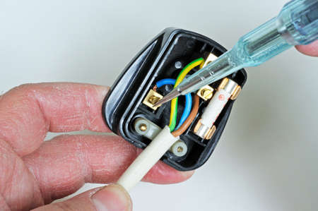 Man wiring English 3 pin 13 amp plug - inserting neutral wire, England, UK, Western Europe  Stock Photo