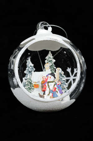 Clear glass Christmas bauble with Winter scene inside against a black background  photo