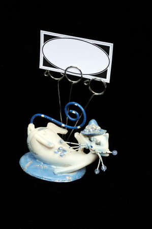 Blue and white cat ornament with business card holders against a black background  photo