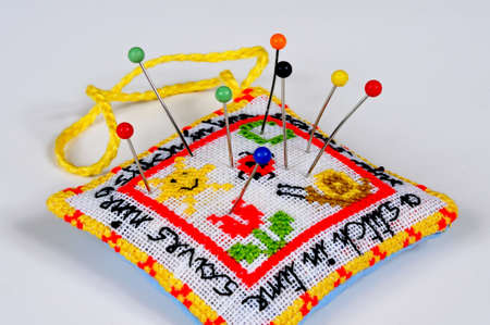 plain stitch: A stitch in time saves nine pincushion with pins against a plain background