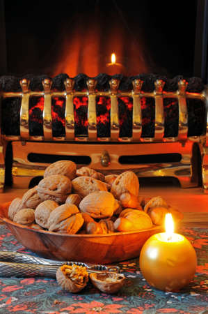 Bowl of walnuts and hazelnuts with a candle and fireplace to the rear, England, UK, Western Europe  photo