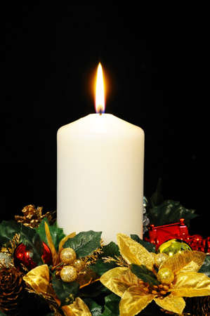 White candle and Christmas flowers against a black background Stock Photo - 20987097