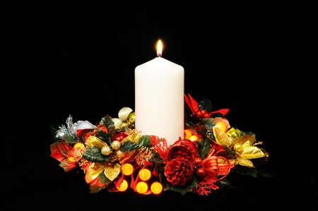 White candle, Christmas flowers and red berry lights against a black background