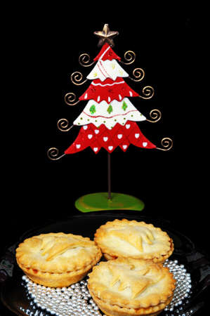 Three homemade mince pies surrounded by edible silver balls with a pretty tin Christmas tree to the rear, England, UK, Western Europe  photo