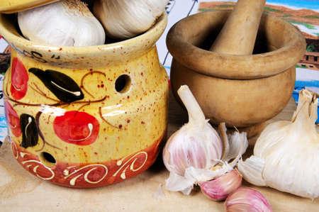 mementos: Ceramic garlic pot, garlic bulbs and pestle and mortar on a wooden chopping board