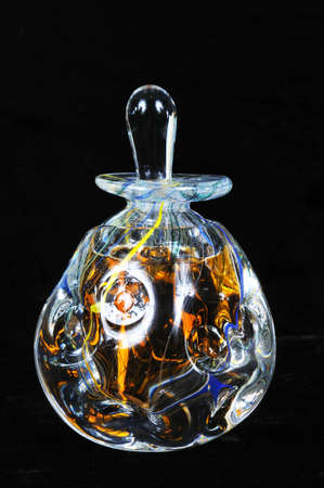 squiggles: Full glass perfume bottle with stopper against a black background  Stock Photo