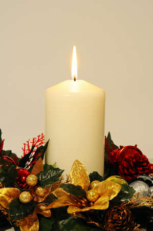 White candle and Christmas flowers against a white background  photo