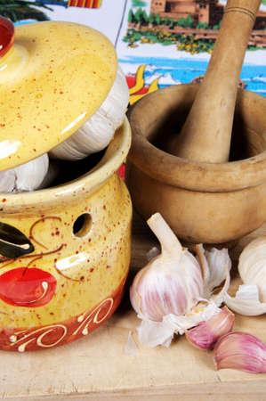 mementos: Ceramic garlic pot, garlic bulbs and pestle and mortar on a wooden chopping board, Calypso, Costa del Sol, Malaga Province, Andalucia, Spain, Western Europe