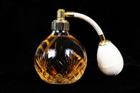 globular: Cut glass perfume atomiser bottle against a black background  Stock Photo