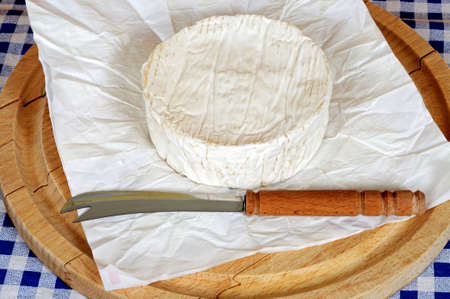Whole French Camembert on a round wooden chopping board  photo