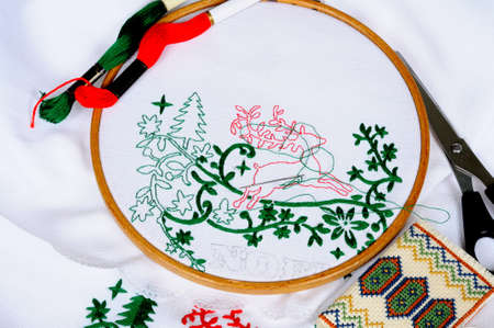White tablecloth in a round frame being embroidered with Christmas scene