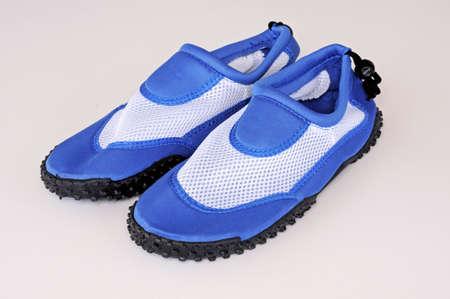 stretchy: Gents blue beach shoes against a plain background