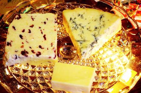 wensleydale: Azul Stilton, Wensleydale con los ar�ndanos y quesos Cheddar en un soporte de placa de vidrio con los regalos de Navidad en la parte trasera, Inglaterra, Reino Unido, Europa Occidental Foto de archivo