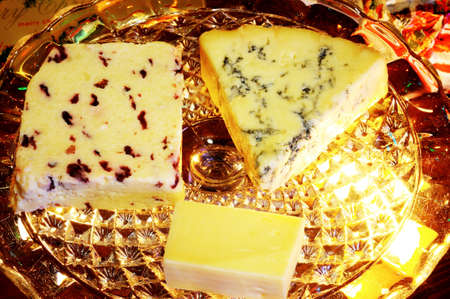 wensleydale: Blue Stilton, Wensleydale with cranberries and Cheddar cheeses on a glass plate stand with Christmas presents to the rear, England, UK, Western Europe