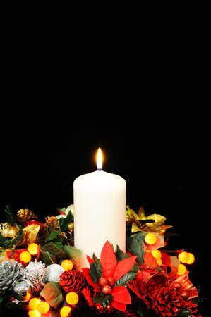 White candle, Christmas flowers and red berry lights against a black background Stock Photo - 21854189