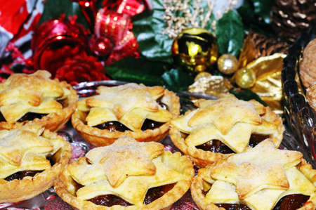 Homemade mince pies with Christmas decorations to the rear, England, UK, Western Europe