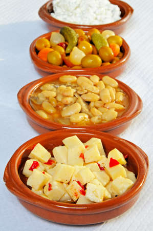 cubed: Tapas – Cubed Manchego cheese in olive oil with chilli, white beans and pork  Alubias con Morro , Green olive cocktail and potato salad to the rear, Urb  Calypso, Costa del Sol, Malaga Province, Andalucia, Spain, Western Europe  Stock Photo