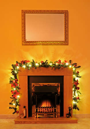 Coal effect fire with wooden surround and Christmas garland, Spain, Western Europe  photo
