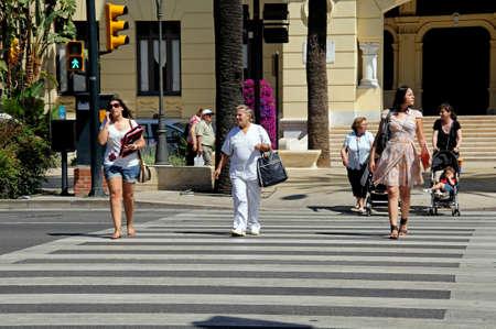 crossings: Malaga, Spain - June 14, 2011 - People crossing the road at a pedestrian crossing, Malaga, Costa del Sol, Malaga Province, Andalucia, Spain, Western Europe  Editorial