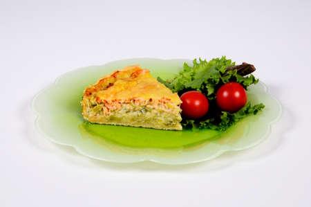 Gerookte zalm en prei taart met salade op een groene plaat Stockfoto